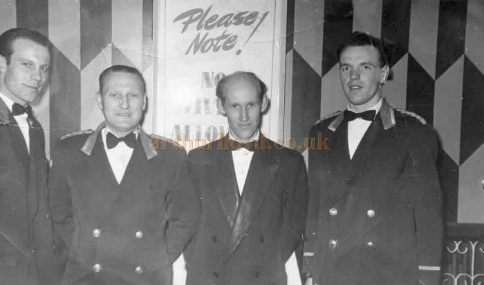A photograph of the FOH door staff at the Astoria Theatre, Charing Cross Road, in the 1950s - Courtesy Christine Laurie whose father, James Millgate, is second from left and the gentleman in the middle is her partner's father Lorne Laurie. The sign behind them appears to say 'Please Note! No Jiving Allowed.'