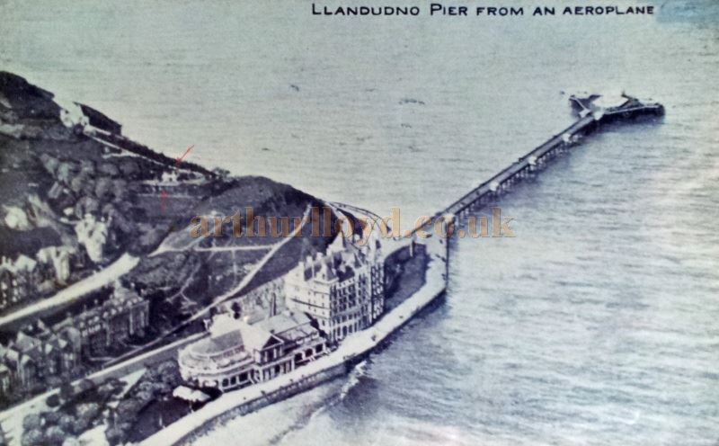 A Postcard showing the Llandudno Pier from an aeroplane. The Happy Valley Theatre can also be seen in this image (See red arrows) - With Kind Permission Llandudno Library.